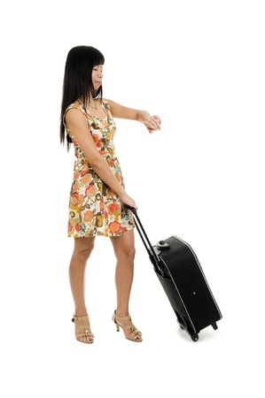 woman with hand luggage checking the time, isolated on white background photo