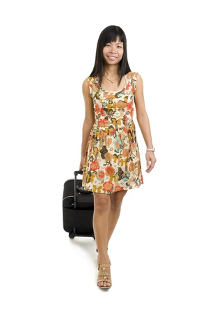 asian woman with hand luggage walking over white photo
