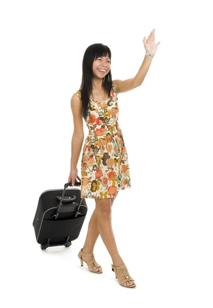 happy woman with small luggage on wheels waving, isolated on white background Stock Photo - 9954683