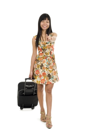 asian woman with hand luggage on wheels walking and pointing at you with her finger, isolated on white background photo