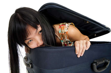 asian woman hidden in luggage, isolated on white background photo