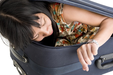 asian woman hidden in luggage checking her watch, isolated on white background photo