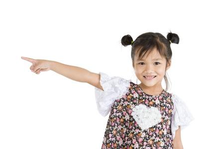 ragazza che indica: sorridente bambina che punta al lato, isolato su sfondo bianco