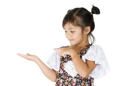 kid pointing: cute Asian girl looking and pointing at something in her hand, isolated on white background