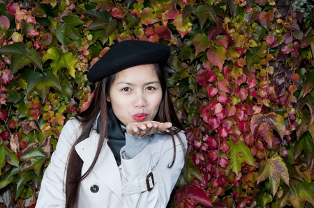pretty young woman throwing a kiss in autumn photo