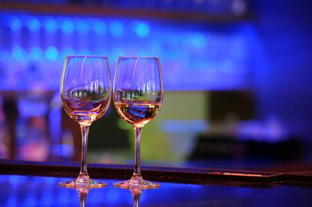 ambient light: two wine glasses on a bar with beautiful ambient light Stock Photo