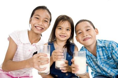 tomando leche: tres niños asiáticos con vasos de leche, aislado en fondo blanco