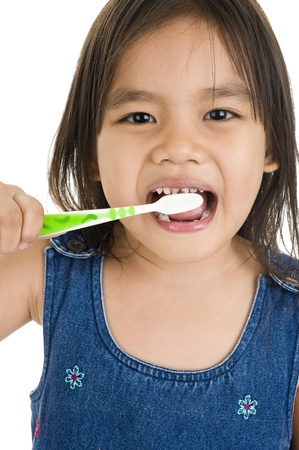 little asian girl brushing her teeth, isolated on white photo