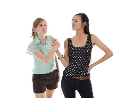 mirada triste: dos mujeres dando la mano sin ser feliz, aislado sobre fondo blanco Foto de archivo