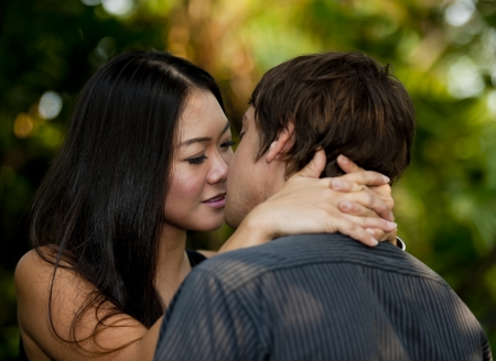 asian woman kissing caucasian man photo