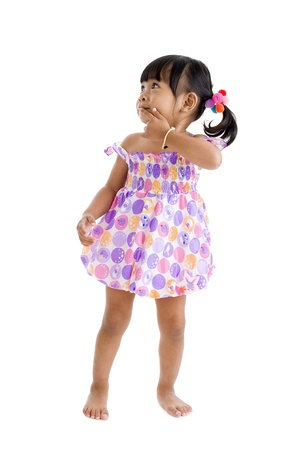 little girl dress: cute asian girl looking to the side with finger on her lips