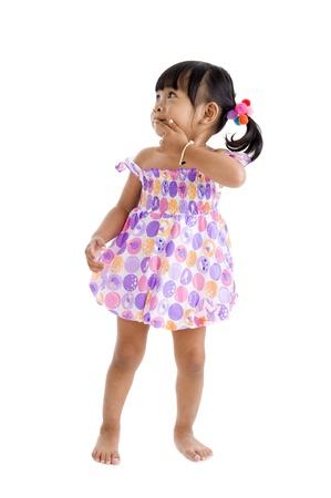petite fille avec robe: mignonne petite fille asiatique regardant sur le côté avec le doigt sur ses lèvres