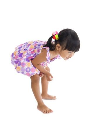 굽힘: 어린 소녀는 뭔가에 대해 자세히 살펴해야하는 절곡 스톡 사진