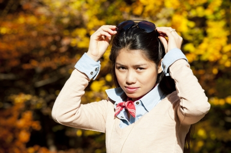 beautiful young asian woman on a sunny day in fall photo