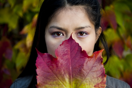 asian beauty behind a colorful maple leaf photo