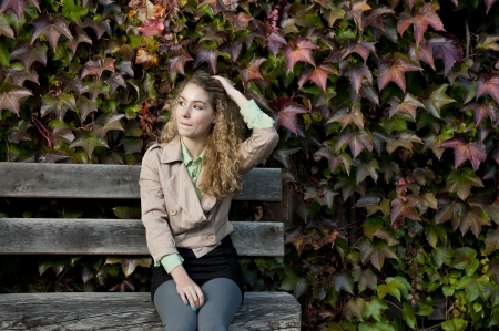 beautiful teen sitting on a bench in autumn season photo