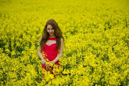 oilseed rape: teenager beauty with red dress in canola field  Stock Photo
