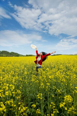 happy asian woman in a canola field photo