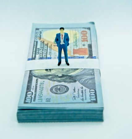 Figure of a man in a suit on top of a wad of hundred dollar bills in a white background