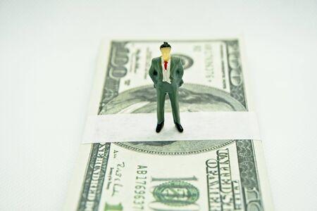 Figure of a man in a suit on top of a wad of hundred dollar bills in a white background