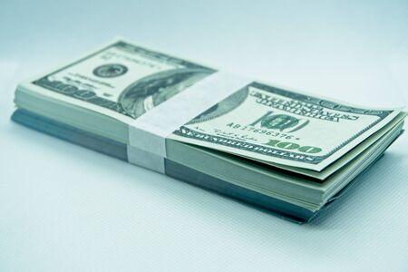 wad of 100 dollar bills in a white background