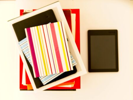Pile of text books and books next to an e-book on a white background