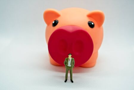 Figure of a man standing in front of a piggy bank in a white background