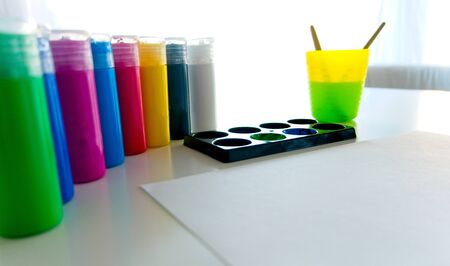 White paper with several containers of acrylic paint and a plastic cup with water and brushes inside