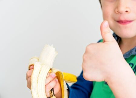 Caucasian boy eating a banana and with his thumb up showing he's okay with a white background