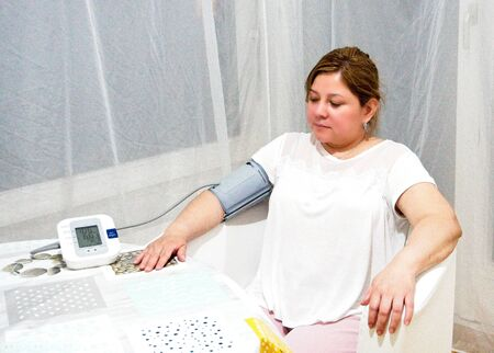 Woman sitting in a chair with her arm resting on a table while taking her blood pressure with an electronic machine in a room with white curtains Stock Photo