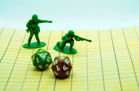Role-playing board with pentagonal-shaped colored dice and miniatures on top of the field