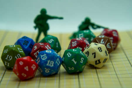 Role-playing board with pentagonal-shaped colored dice and plastic figures on top of the board