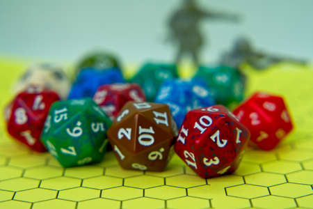 Role-playing board with pentagonal-shaped several colored dice and plastic figures on top of the board