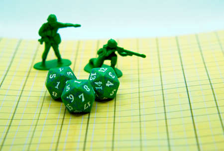 Role-playing board with pentagonal-shaped green dice and plastic figures on top of the board Banco de Imagens