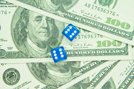 Two blue dices on top of hundred dollar bills.