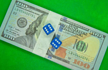 Two dices on top of hundred dollar bills with a green background Stockfoto