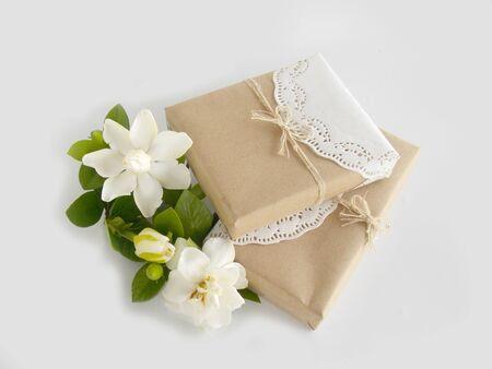 Gift box with white gardenia flower on white background