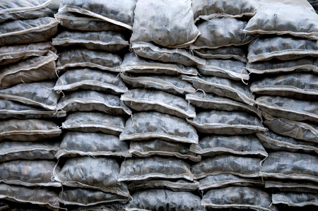 smooth stones: landscaping  with weathered smooth stones in assorted shapes and sizes in bag stacked
