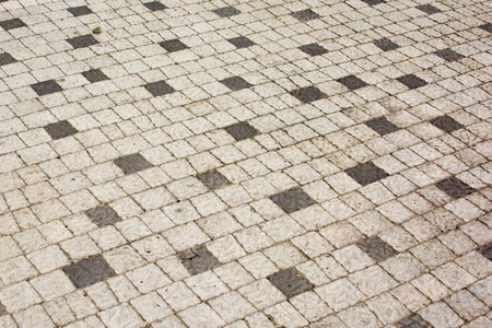Cobbles of white and black squares, An old road paved with stone. Beautiful background.