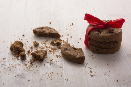 brocken: A stack of Christmas chocolate cookies tied a red ribbon. Broken cookies, a lot of crumbs on the table.
