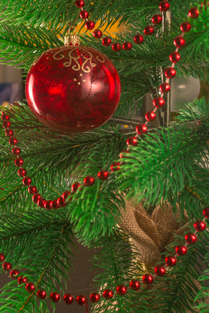 A Christmas tree decorated with beads and one red glass ball. A transparent New Years ball. Beautiful christmas background. Stock Photo