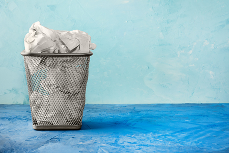 A trash can for paper. Beautiful background with place for text. A full trash can for crumpled paper sheets.