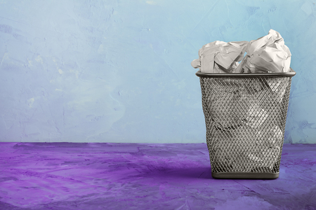A trash can for paper. Beautiful unusual background with place for text. A full trash can for paper sheets.