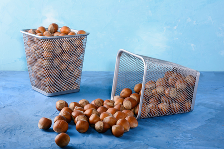 Hazelnut scattered on the table. Nuts in a two metal basket. Beautiful background.