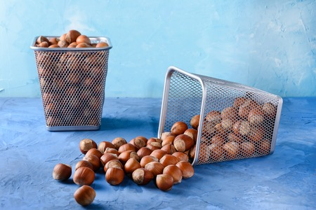 Hazelnut scattered on the table.Beautiful blue background. Nuts in baskets.