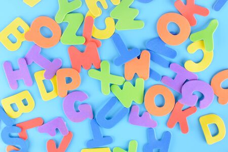 Background of multi-colored letters. Chaotically scattered alphabet.