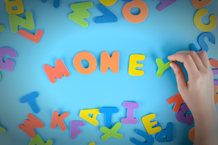The girl puts the word money out of colorful letters. Beautiful background.