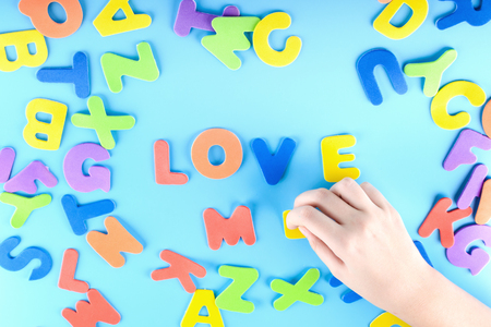 The girl puts out of the multicolored letters the words love me . Beautiful background.