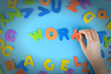 The girl puts out of the multicolored letters the words work. Beautiful background with vignette..