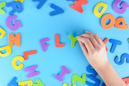 The girl puts out of the multicolored letters the words fly . Beautiful background. Фото со стока